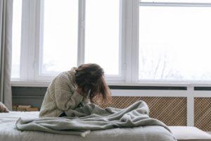 donna triste sul letto